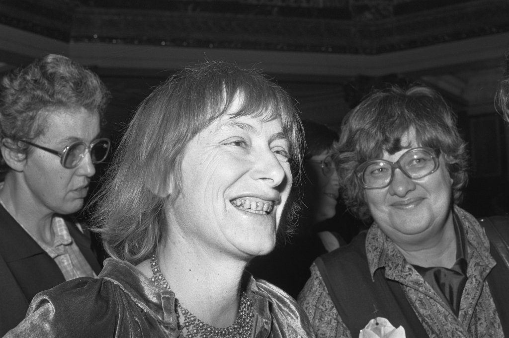 A black and white image of three women in 1980s attire. Soelle, centre, smiles in conversation with someone out of the frame.
